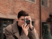 The young man model in a coat photographs the vintage camera stock photography