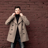 The young man model in a coat poses at a brick wall. Toned Royalty Free Stock Image
