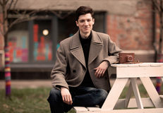 The young man model in a coat sits at a white table with the vintage camera outdoors Royalty Free Stock Images