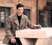 The young man model in a coat sits at a white table with the vintage camera outdoors Stock Photos