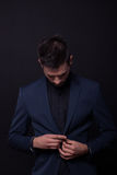 Young man model looking down buttoning jacket suit Royalty Free Stock Image