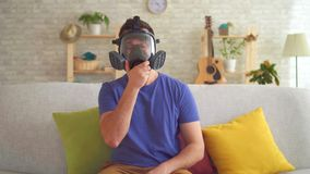 Young man in a modern apartment feels a bad smell and puts on a respirator