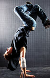 Young man modern dance. On dark wall background stock image