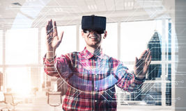 Young man in modern office interior experiencing virtual reality Royalty Free Stock Photography
