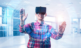 Young man in modern office interior experiencing virtual reality Royalty Free Stock Images