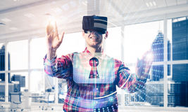 Young man in modern office interior experiencing virtual reality Stock Photo