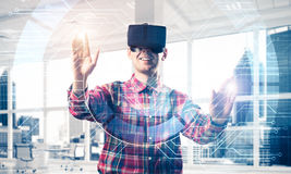 Young man in modern office interior experiencing virtual reality Royalty Free Stock Photo