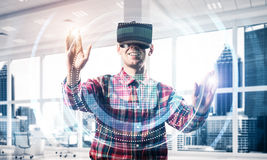 Young man in modern office interior experiencing virtual reality Stock Images
