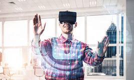 Young man in modern office interior experiencing virtual reality Royalty Free Stock Image