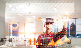 Young man in modern office interior experiencing virtual reality technology Stock Images