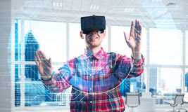 Young man in modern office interior experiencing virtual reality technology Stock Image