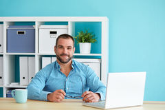 Young man in modern office with laptop stock photo