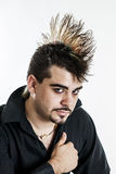 Young man with mohawk hairdo. Portrait of a mid 20s young punk man with a mohawk hairdo and guyliner isolated on a white background stock photo