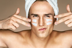 Young man with moisturizer cream on the face. royalty free stock photos