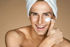 Young man with moisturizer on the face. royalty free stock photography