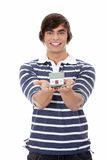 Young man with money and house's model. Stock Photo