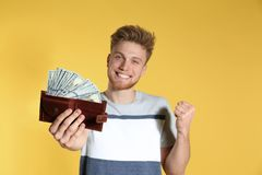 Young man with money in wallet on color background. Space for text stock photos