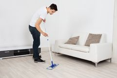 Young Man Mopping Floor At Home Stock Photos