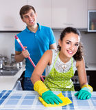Young man mopping and smiling woman dusting. Young men mopping and smiling women dusting in domestic kitchen Royalty Free Stock Images