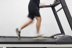Young man in motion on a treadmill in the gym. Image of young man in motion on a treadmill in the gym Royalty Free Stock Photos