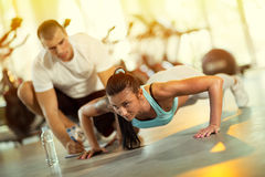 Young man motivating gym woman. Young men motivating gym women  during push ups exercise Royalty Free Stock Images