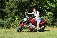 Young man on motorbike. Young man sitting on a new modern red motorbike standing on green grass in front of bush Royalty Free Stock Image