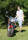 Young man with motorbike. Young man standing by a new modern red motorbike standing on green grass in front of bush Royalty Free Stock Photos