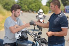 Young man on motorbike talking with instructor. Young men on motorbike talking with his instructor Royalty Free Stock Photography