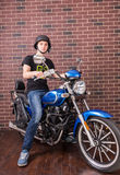 Young Man on Motorcycle in front of Brick Wall Royalty Free Stock Images