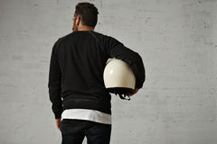 Young man with motorcycle helmet. Back shot of a sexy young man with a hip haircut and beard holding a blank white shiny motorcycle helmet against a rough white Royalty Free Stock Image