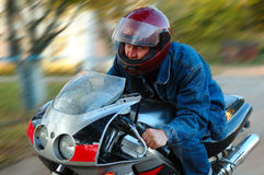 Young man on motorcycle (motorbike). Young man on motorcycle (motorbike) with blurred background (motion blur stock photography