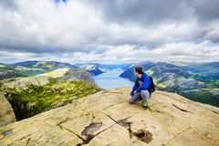 A young man on the mountain admiring view over Lysefjord. Norway. Royalty Free Stock Photography