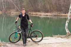Young man on mountain bike relaxes, on background flooded mine Royalty Free Stock Photography