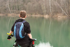 Young man on mountain bike relaxes, on background flooded mine Royalty Free Stock Photo