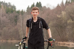 Young man on mountain bike relaxes, on background flooded mine Stock Photo