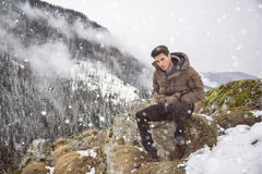Young man at mountain sitting under snow Royalty Free Stock Photos