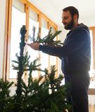 Young man mounting artificial Christmas tree Royalty Free Stock Image
