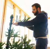 Young man mounting artificial Christmas tree Royalty Free Stock Images