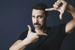 Young man with moustache framing his face with his hands Royalty Free Stock Photos