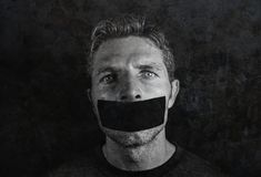 Young man with mouth and lips sealed covered with adhesive tape in censorship coerced freedom of speech and forced silence and sec. Recy concept on grunge black stock image