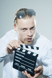 Young man with movie clapper Royalty Free Stock Photography
