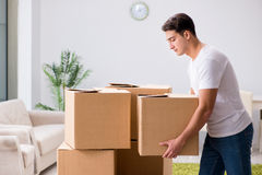 The young man moving boxes at home. Young man moving boxes at home Stock Image