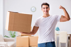 The young man moving boxes at home Stock Photography
