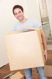 Young man on moving day carrying cardboard box Royalty Free Stock Images