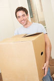 Young man on moving day carrying cardboard box Stock Images