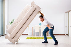 The young man moving furniture at home. Young man moving furniture at home Stock Photo