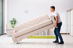 The young man moving furniture at home Royalty Free Stock Image