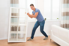 Young Man Moving Shelf Royalty Free Stock Photography