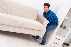 The young man moving sofa couch Royalty Free Stock Image