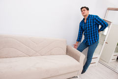 The young man moving sofa couch Royalty Free Stock Photography